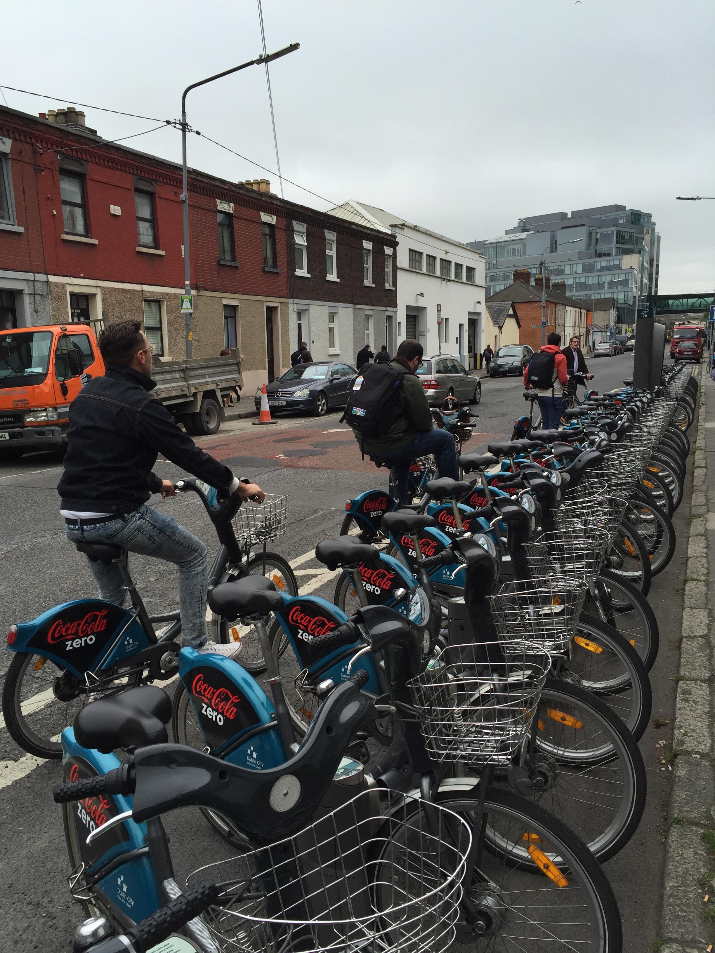 Three men waiting to dock their bikes at bike rack