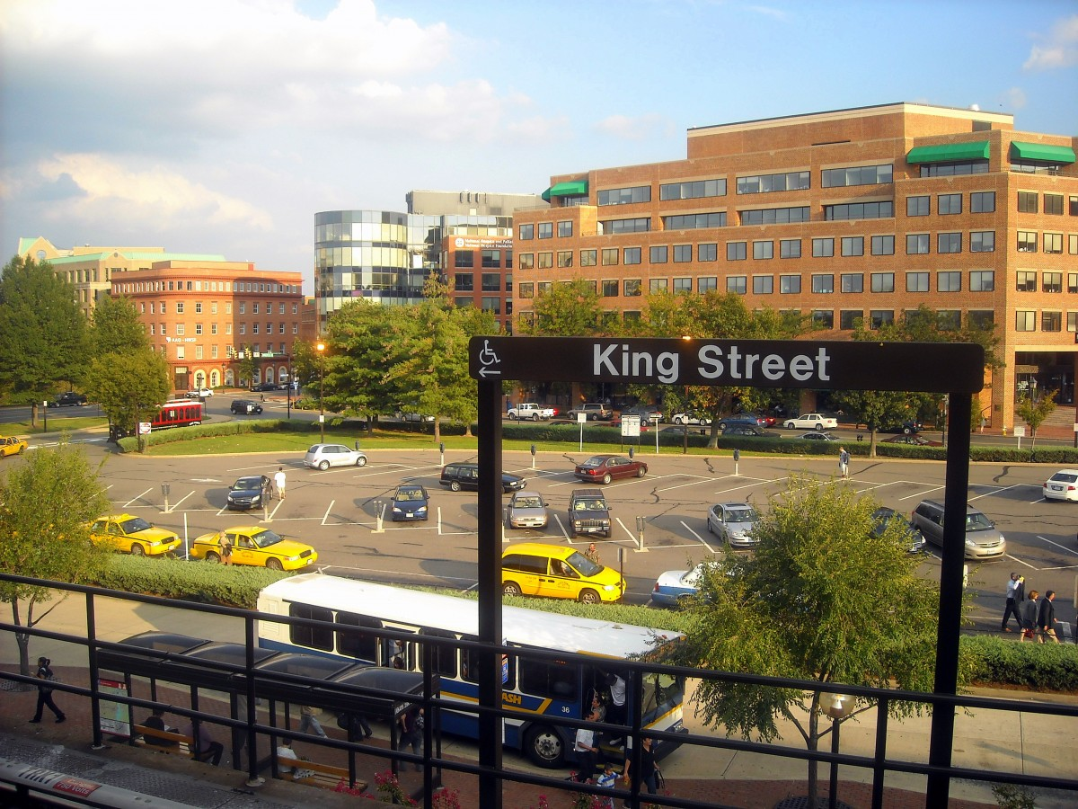 at the king street metro parking is out and a pedestrian